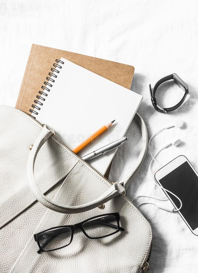 Het leerhandtas van vrouwen, schone lege blocnote, pen, glazen, smartphone, horloge op een lichte achtergrond, hoogste mening Vri stock afbeelding