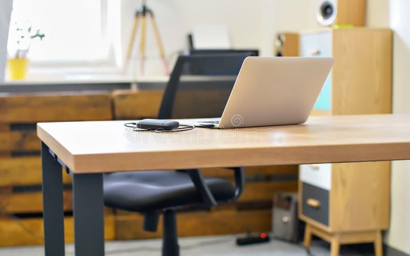 Het lege bureau, laptop met aangesloten generisch usbapparaat op het, vertroebelde stoel en meubilairachtergrond royalty-vrije stock fotografie