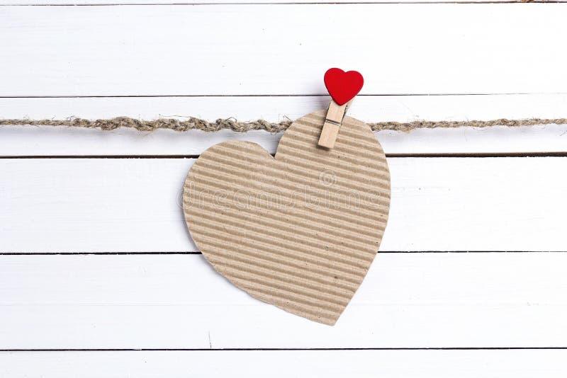 Het lege document hart-kaart hangen op wasknijpers op witte houten bedelaars stock foto's