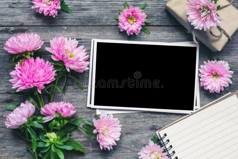 Het lege fotokader met mooi boeket van roze aster bloeit, blocnote en giftdoos Spot omhoog lay-out flatlay royalty-vrije stock fotografie