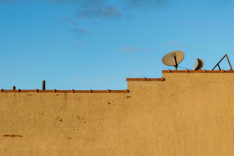 Het lege geschilderde bakstenen muur en terracottakleidakwerk betegelt dakspanen, en een paar oude satelliettv-ontvangersschotels stock foto's