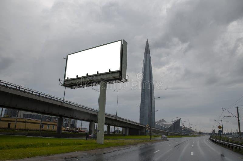 Het lege grote witte scherm voor uw make-up, reclame, product, tekst op de achtergrond van high-rise gebouwen in de economische s stock foto