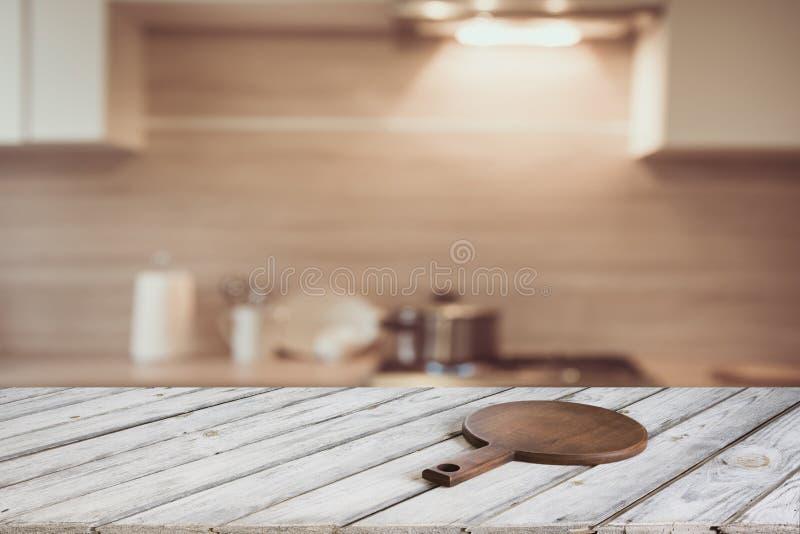 Het lege houten tafelblad met scherpe raad en defocused moderne keuken voor vertoning of montering uw producten royalty-vrije stock afbeeldingen