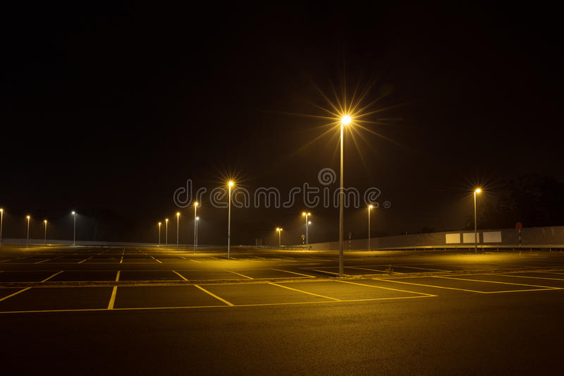 Het lege openluchtparkeerterrein bij nacht glanste met straatlantaarns royalty-vrije stock afbeelding