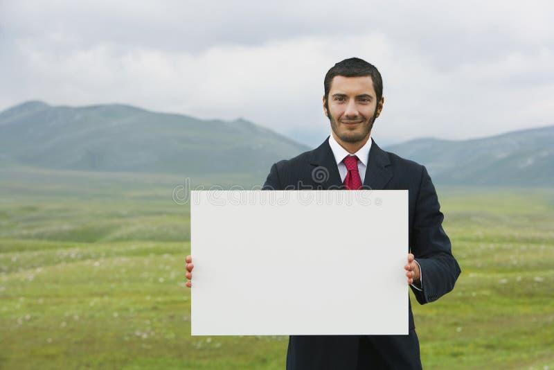 Het Lege Teken van de zakenliedenholding op Berggebied stock afbeelding