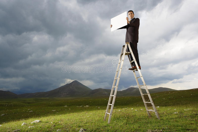 Het Lege Teken van zakenmanon ladder holding royalty-vrije stock fotografie