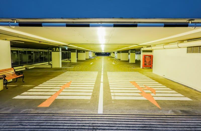 Het lege verlichte ondergrondse binnenland van het autoparkeren onder moderne wandelgalerij en pijlen op vloer stock afbeelding