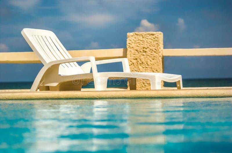 Het lege witte plastiek sunbed naast pool royalty-vrije stock afbeelding