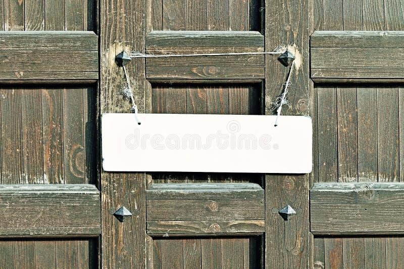 Het lege witte teken hangen met kabel aan flarden op de oude bruine houten muur met metaalklinknagels - achtergrond in retro tone stock afbeeldingen