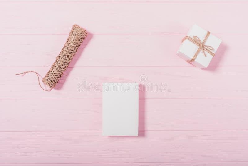 Het lege witte vakje bond dichtbij gift en streng op roze houten lijst stock afbeelding