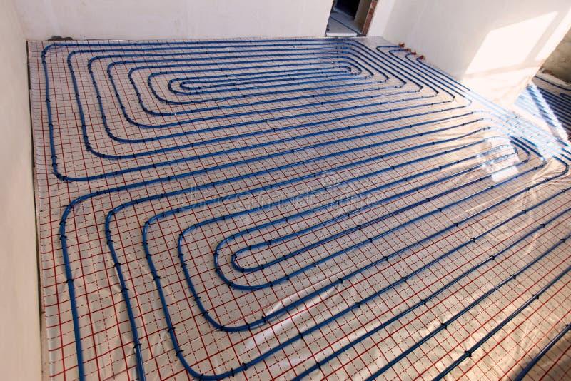 Het leggen van blauwe pijpen voor vloer het verwarmen bij de bouwwerf stock foto's