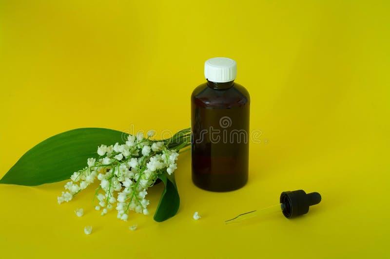 Het lelietje-van-dalen, majalis van etherische olieconvallaria haalt, remedie met verse bloemen Convallaria op een gele achtergro stock foto
