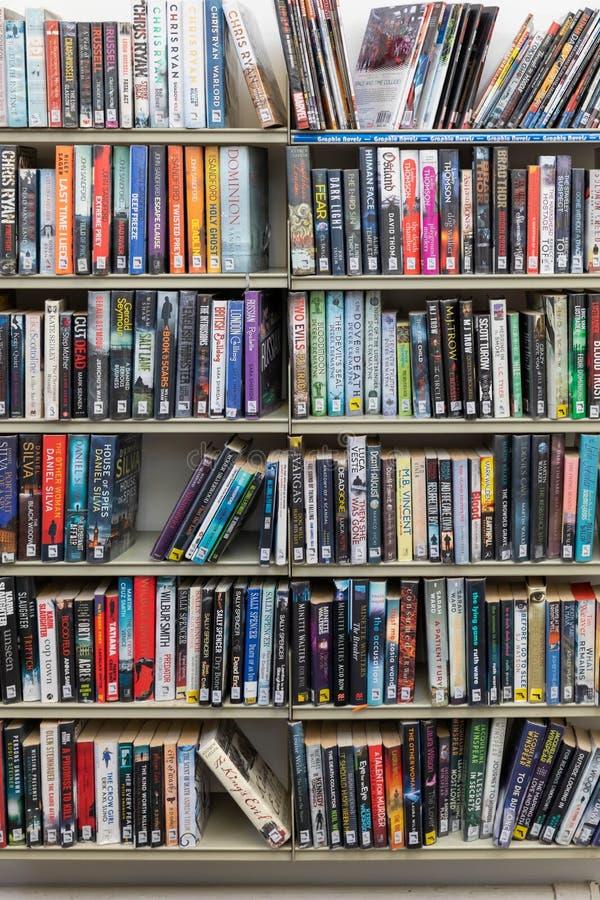 Het lenende hoogtepunt van bibliotheekplanken van boeken royalty-vrije stock foto's