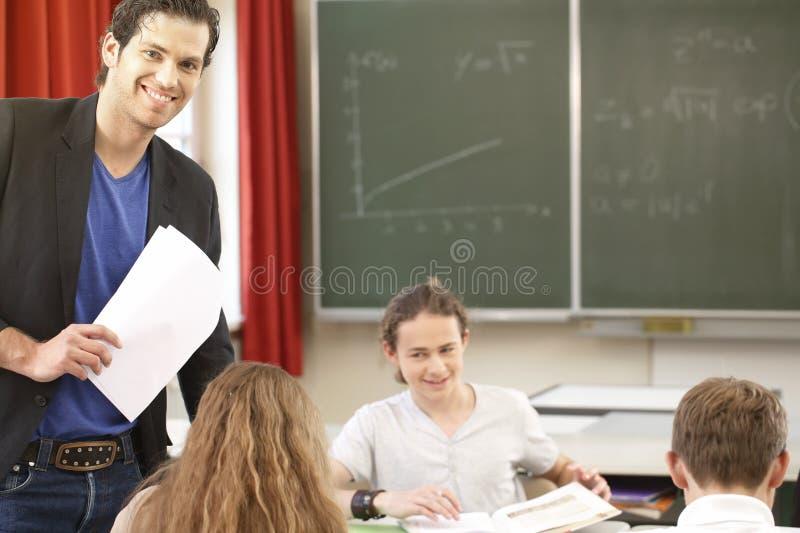 Het leraarsonderwijs of leidt bij de raad een klasse in school op stock foto
