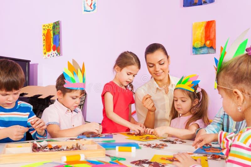 Het leraarswerk met jonge geitjes in kunst peuterklasse royalty-vrije stock afbeeldingen