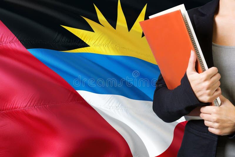 Het leren Barbudan taalconcept Jonge vrouw die zich met de de Antigua en vlag van Barbuda op de achtergrond bevinden Leraarsholdi royalty-vrije stock foto