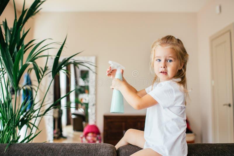 Het leren concepten voor kinderjaren - Weinig blonde aanbiddelijk meisje behandelt thuis haar boom met mistige nevelfles aan wate stock foto