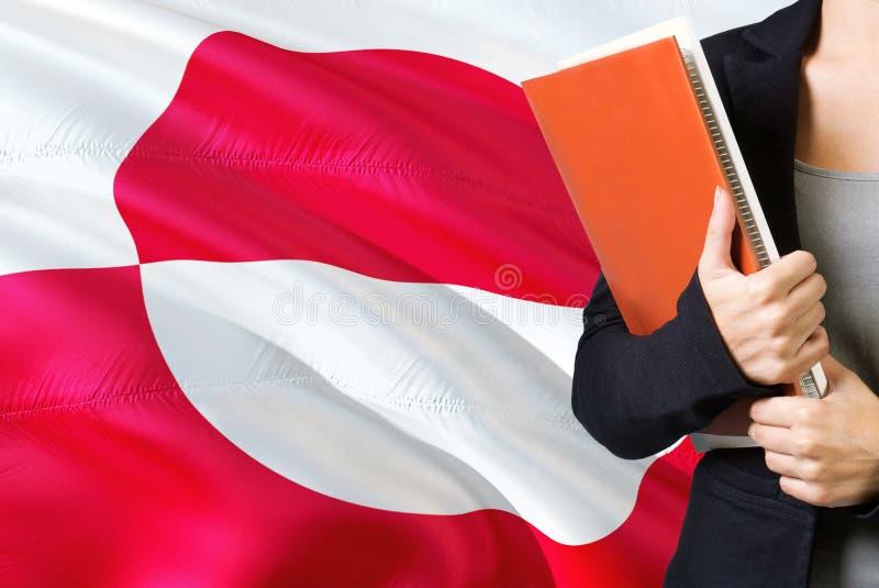 Het leren taalconcept Jonge vrouw die zich met de vlag van Groenland op de achtergrond bevinden De boeken van de leraarsholding,  stock afbeelding