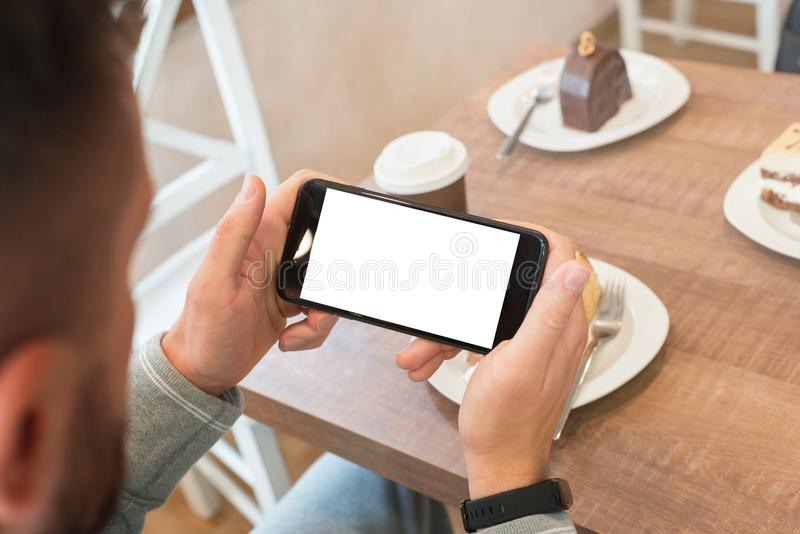 Het letten op film of gelezen nieuws op slimme telefoon in horizontale positie met het geïsoleerde scherm voor model royalty-vrije stock afbeelding