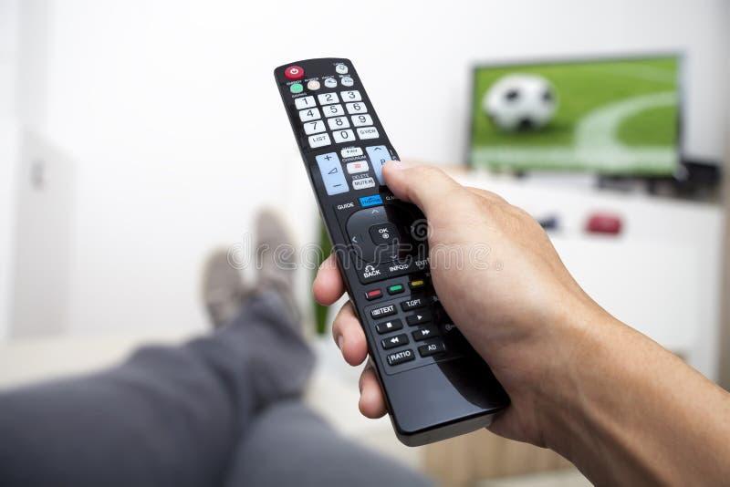 Het letten op TV Afstandsbediening ter beschikking Voetbal stock foto