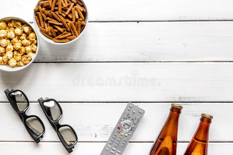Het letten op TV met omhoog spaanders, bier en afstandsbediening op witte achtergrond hoogste meningsspot royalty-vrije stock fotografie