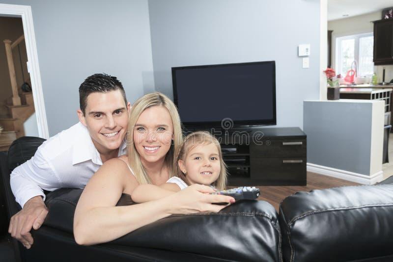 Het letten op TV samen thuis stock fotografie