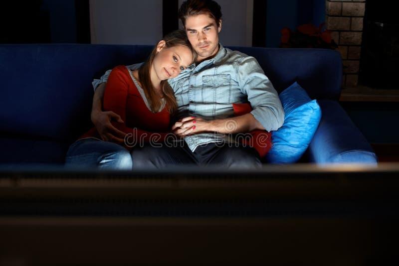 Het letten op van de man en van de vrouw film op TV royalty-vrije stock afbeeldingen
