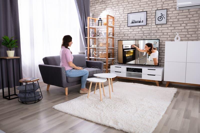 Het Letten op van de vrouw Televisie stock afbeeldingen