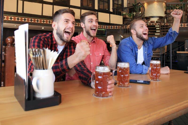 Het letten op voetbal in bar Gelukkige vrienden die bier drinken en voor favoriet team, het vieren overwinning toejuichen stock foto