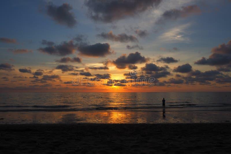Het letten op zonsondergang op het strand Thailand stock foto