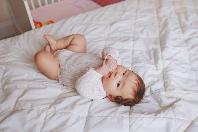 Het leuke aanbiddelijke Aziatische gemengde meisje van de rasbaby vier maanden oud die op bed liggen royalty-vrije stock foto's