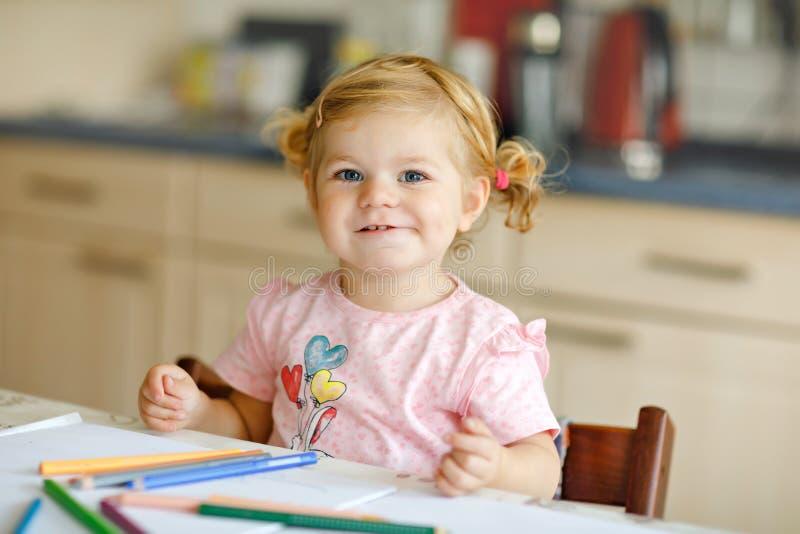 Het leuke aanbiddelijke babymeisje het leren schilderen met potloden Weinig tekening van het peuterkind thuis, gebruikend kleurri stock afbeeldingen