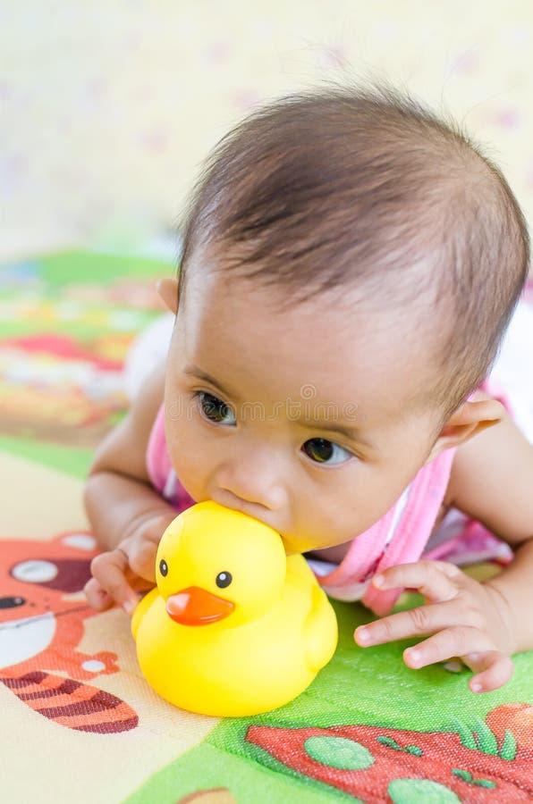 Het leuke Aziatische babymeisje spelen met het stuk speelgoed van de roverseend stock fotografie