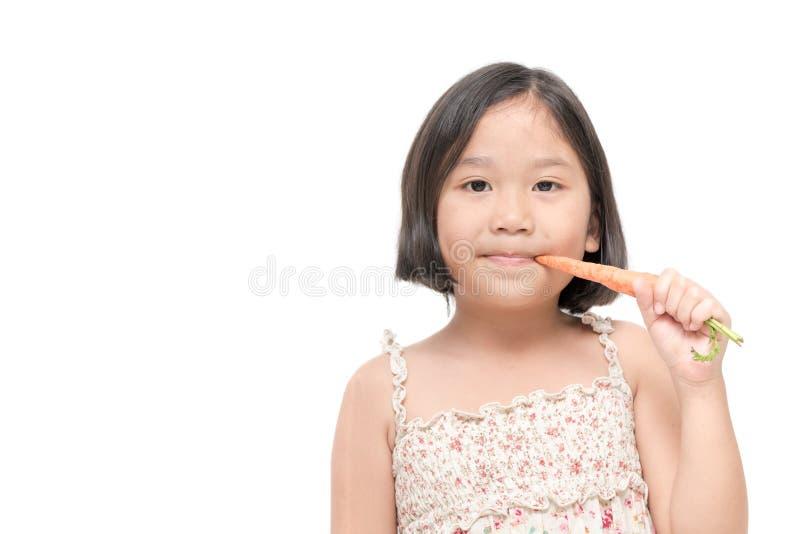 Het leuke Aziatische die meisje eet babywortel op witte achtergrond wordt geïsoleerd stock foto's