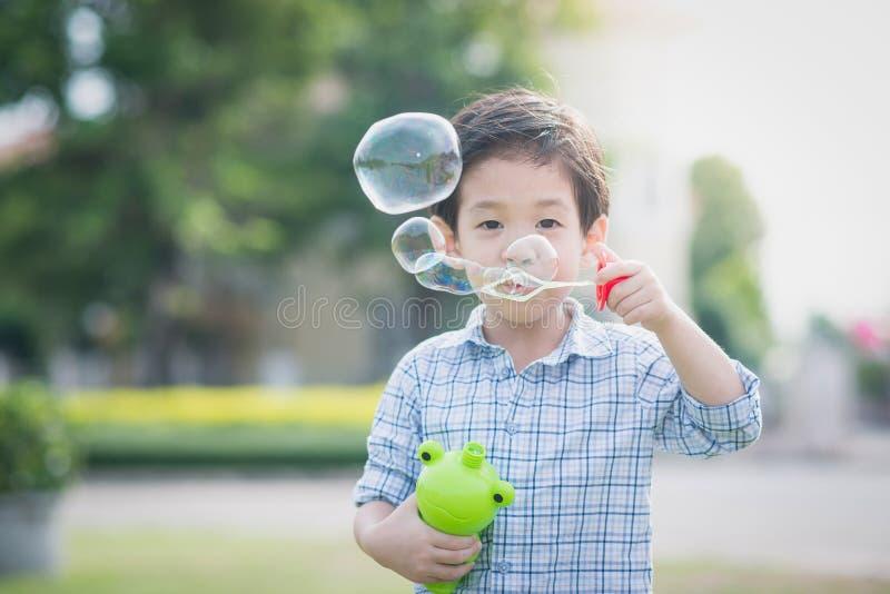 Het leuke Aziatische kind blaast zeepbels stock afbeeldingen