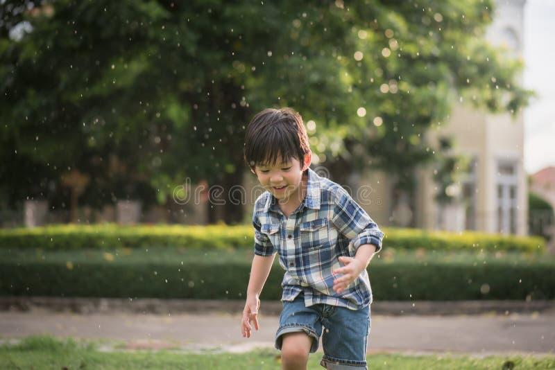 Het leuke Aziatische kind spelen in het park stock foto