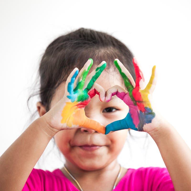 Het leuke Aziatische kindmeisje met geschilderde handen maakt hartvorm royalty-vrije stock fotografie