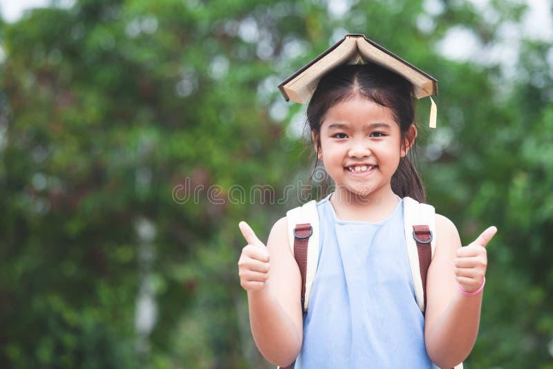 Het leuke Aziatische kindmeisje met schooltas zette een boek op hoofd stock foto