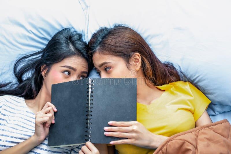 Het leuke Aziatische lesbische boek van de paarlezing samen en liggend op bed Levensstijlen en minnaarsconcept Het gelukleven en  royalty-vrije stock afbeelding
