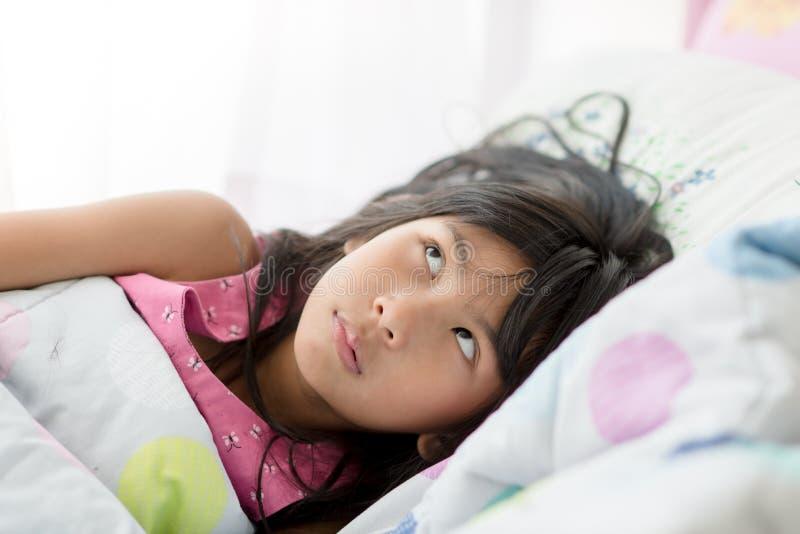 Het leuke Aziatische meisje ontspannen op bed thuis royalty-vrije stock afbeelding