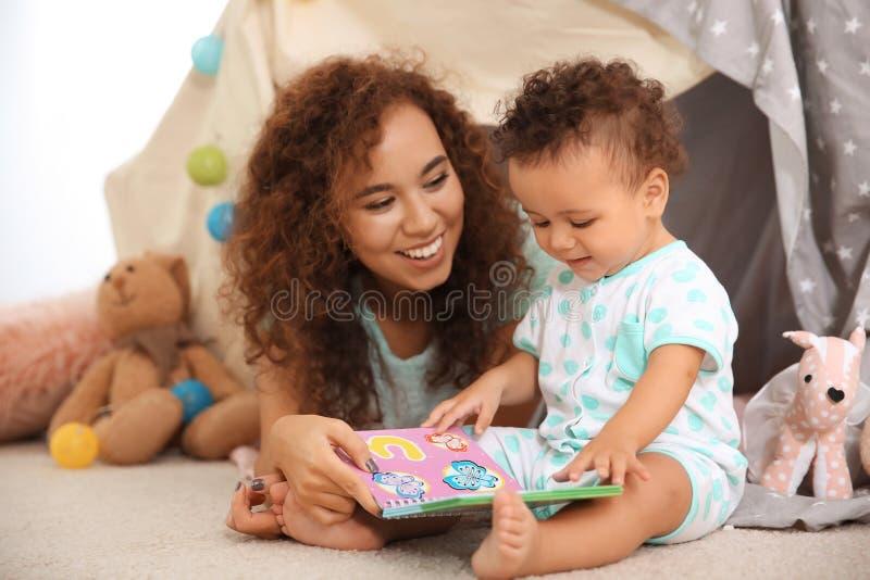Het leuke baby en moeder spelen op vloer stock afbeeldingen