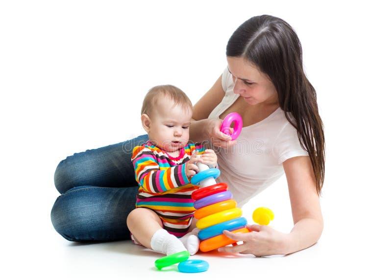 Het leuke baby spelen met haar die moeder op witte achtergrond wordt geïsoleerd stock afbeelding