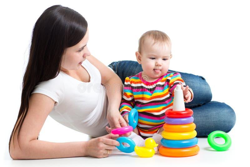 Het leuke baby spelen met haar die moeder op witte achtergrond wordt geïsoleerd stock afbeeldingen