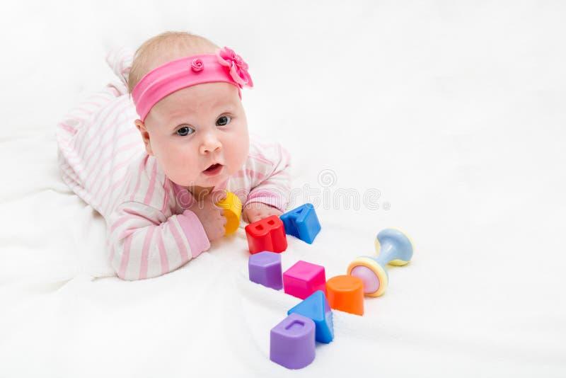 Het leuke baby spelen met kleurrijk stuk speelgoed Nieuw - geboren kind, meisje de camera bekijken en het kruipen die figuur vier stock foto's