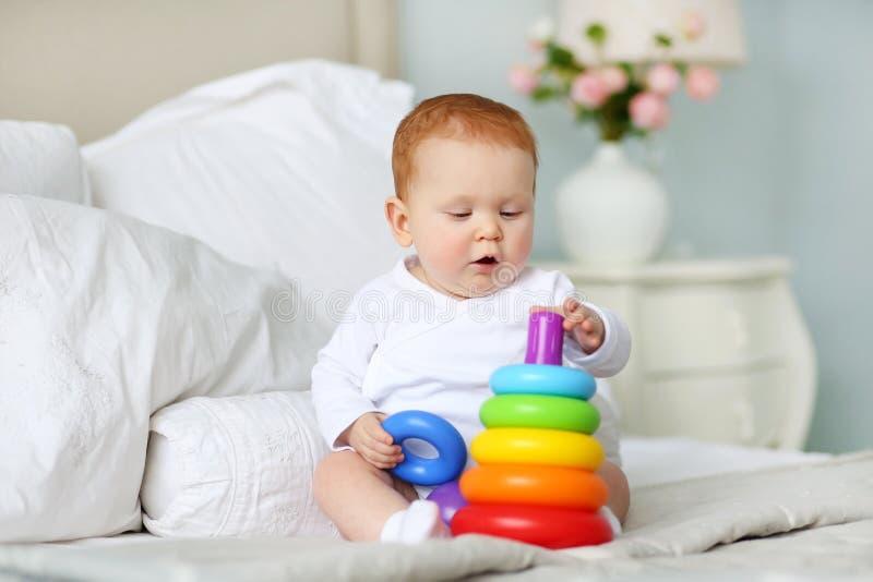 Het leuke baby spelen met kleurrijke regenboogstuk speelgoed piramidezitting op bed in witte zonnige slaapkamer Speelgoed voor kl royalty-vrije stock fotografie