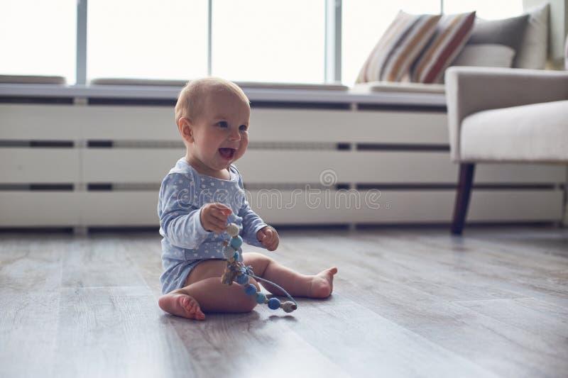 Het leuke babyjongen spelen met gebreid stuk speelgoed op vloer thuis stock afbeelding