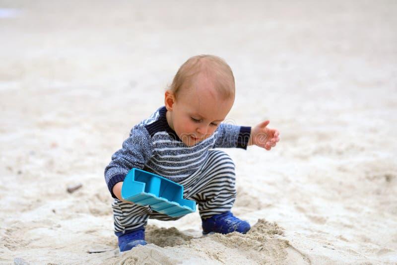 Het leuke Babyjongen Spelen met Zand en Blauwe Plastic Schop stock afbeeldingen