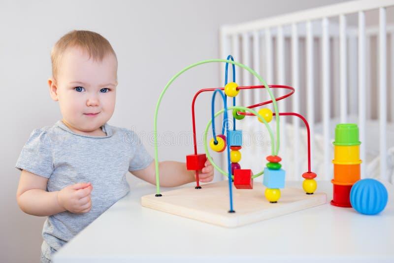 Het leuke babymeisje spelen met speelgoed op de lijst stock fotografie