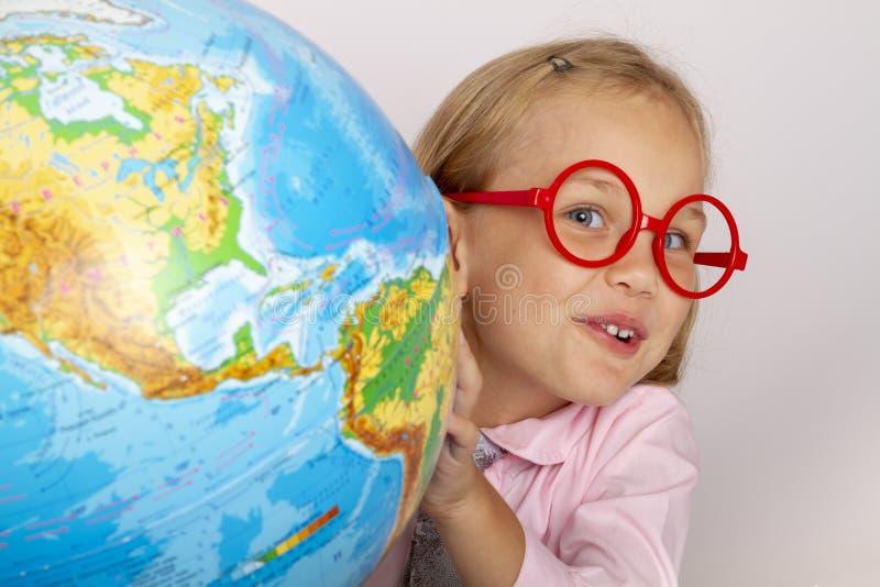Het leuke bedrijvige kind zit binnen bij een bureau stock foto