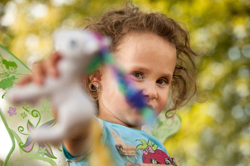 Het leuke blonde meisje speelt met zijn favoriet stuk speelgoed in park, kleurrijke de herfstbladeren op achtergrond, poneystuk s stock foto's